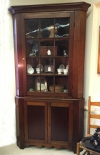 Early New England cherry two part corner cupboard c1800