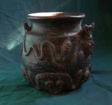 Mexican Black ware decorated storage jar with human heads and serpents